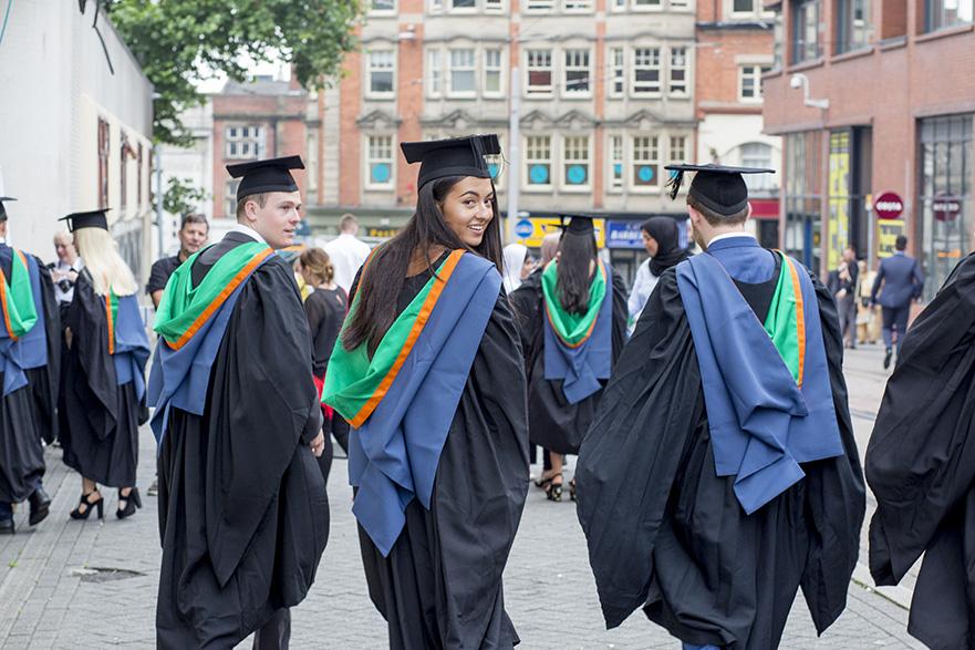 3 graduates walking outside NTU