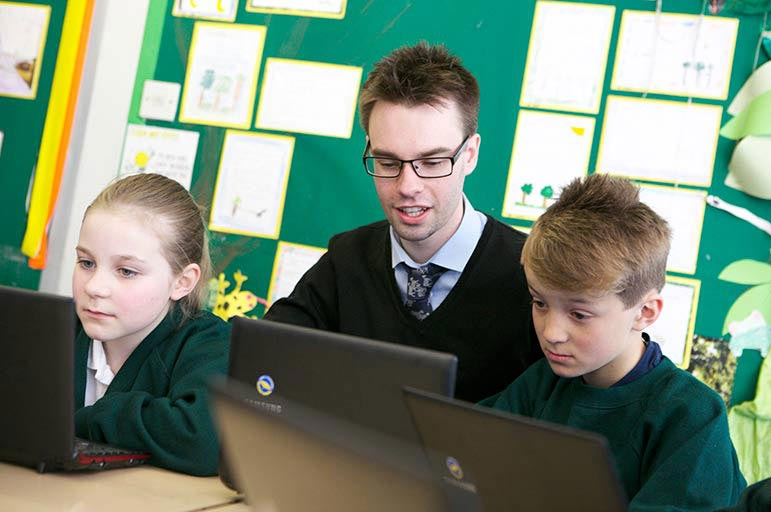 Teacher and pupils using laptops