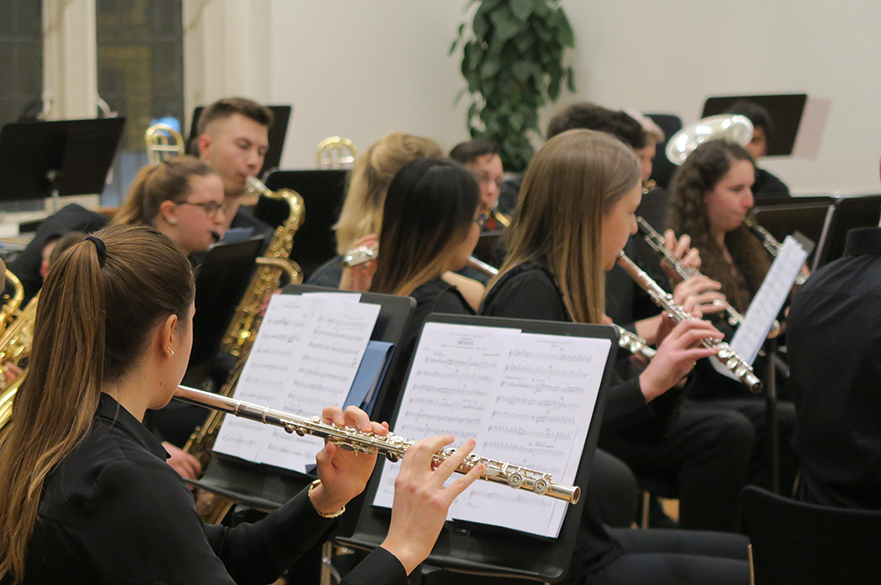 Young men and women sat playing instruments including flutes and saxophones.