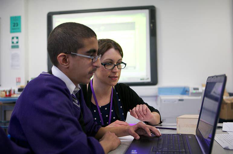 Teacher helping student on laptop