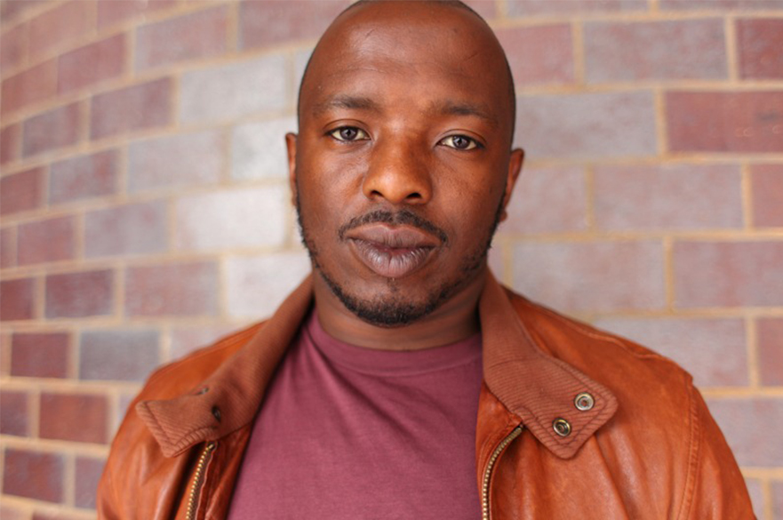 A photo of Nick Makoha standing in front of a brick wall.