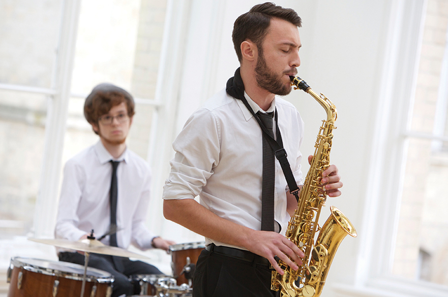 Male student playing a saxophone with another male student playing a drumkit behind.