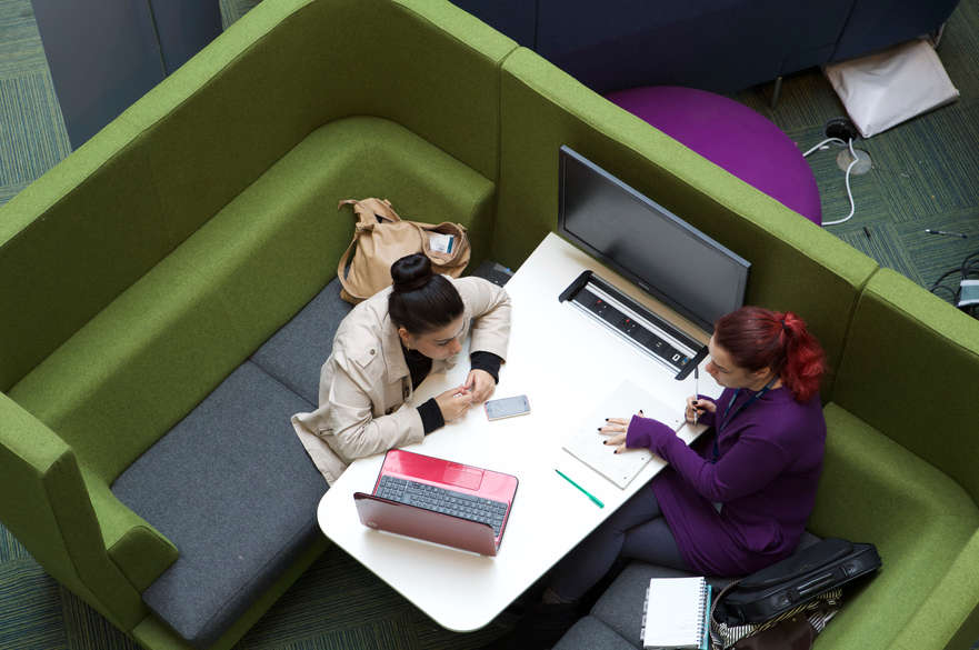 A bids eye view of two people sat opposite each other at a table. One is helping the other with a piece of work.