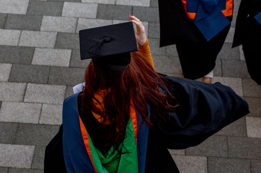 A picture of a girl from behind dressed in a Graduation gown and cap. She has one hand on top of her cap, trying to keep it on her head.