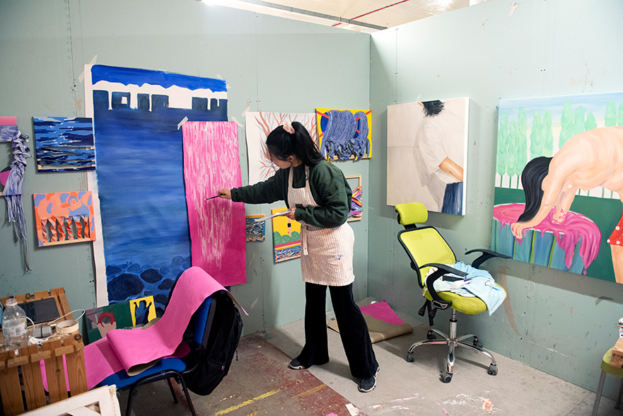 A student painting in a studio with lots of other artwork around.