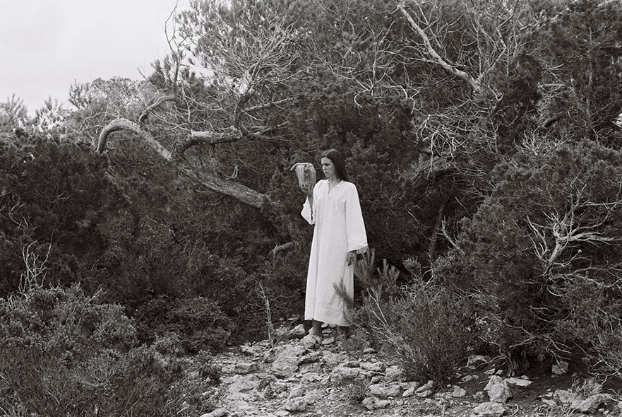 A black and white photo of a woman in a wood holding an animal skull