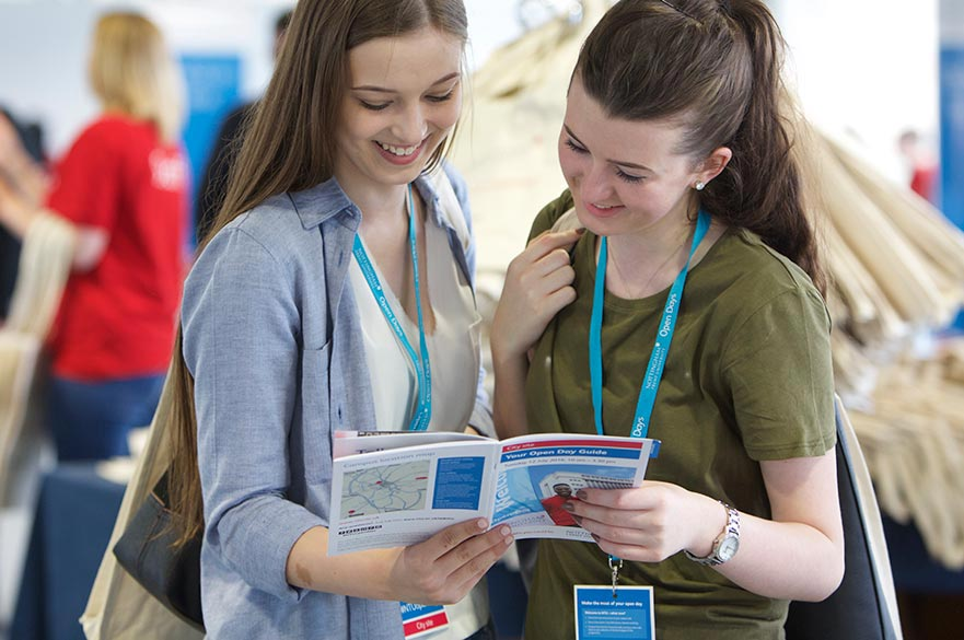 Students reading an open day guide
