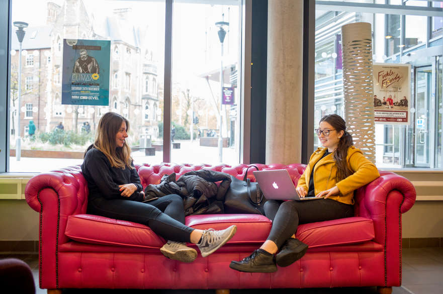 Two female students sat on opposite ends of a sofa
