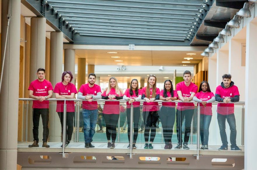 Ten student ambassadors in NTU pink shirts on a glass balcony