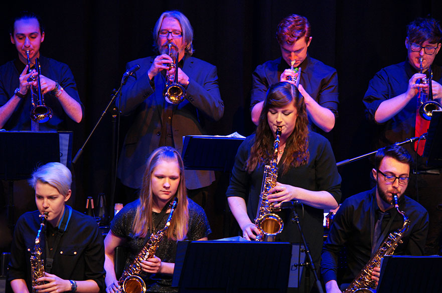 Male and female musicians stood in two lines playing trumpets and saxophones.