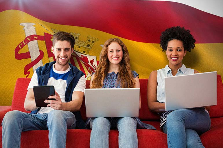 Students using laptops in front of Spanish flag