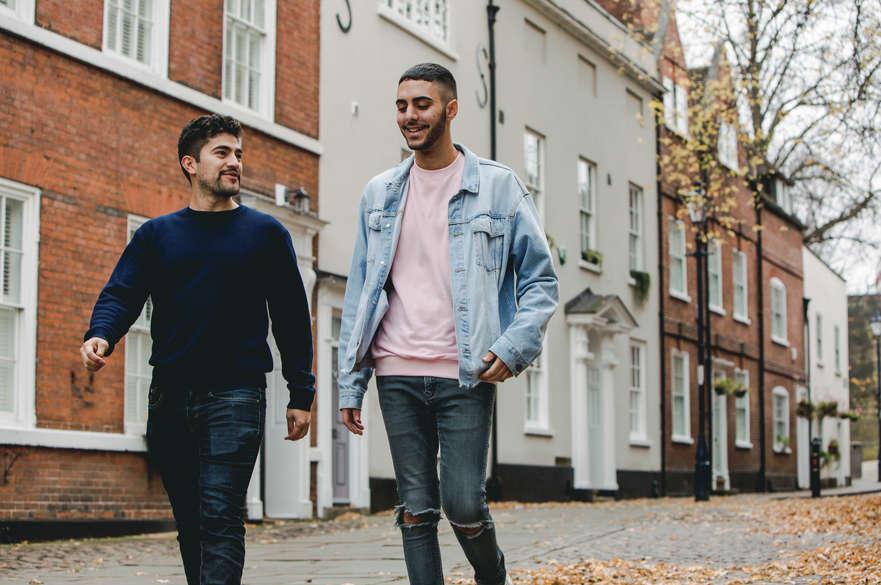 Two male students walk side by side talking down a cobbled street in Nottingham