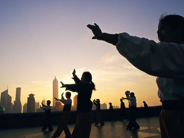 Group doing tai chi on a city rooftop