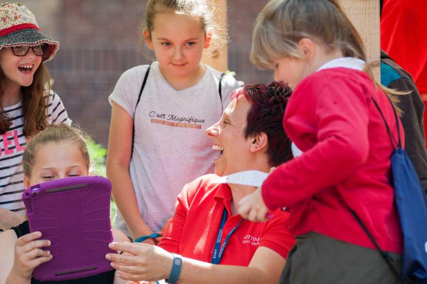smiling teacher with school aged children