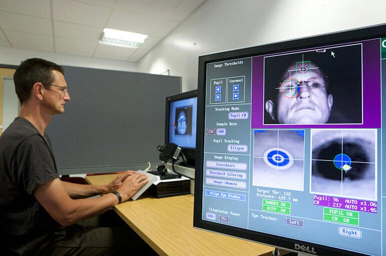 Person using pc with eye tracker technology