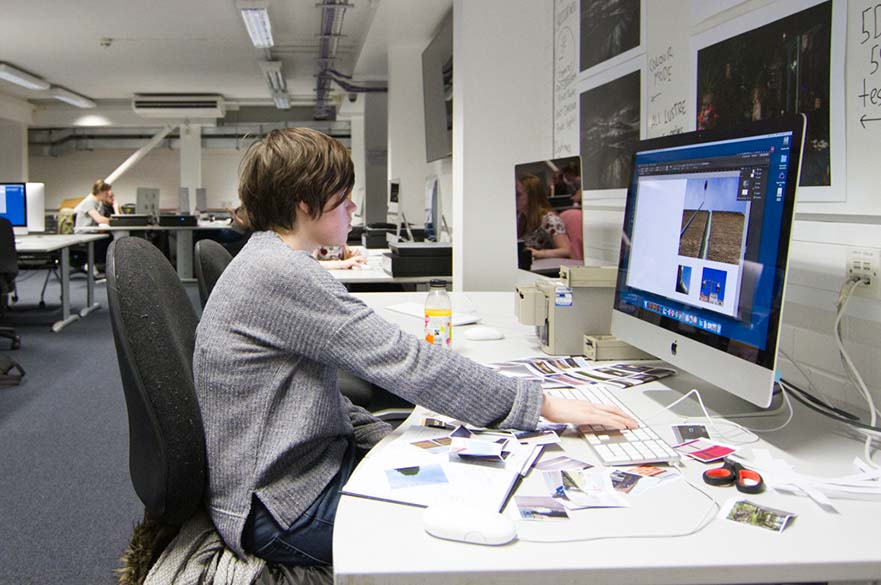 Student working at Mac computer.