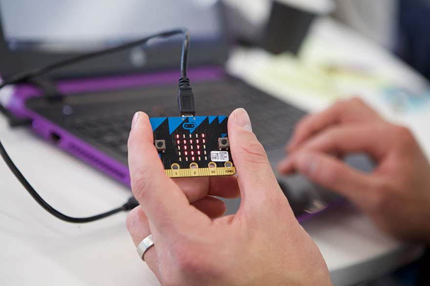 Hand holding a BBC micro:bit computer