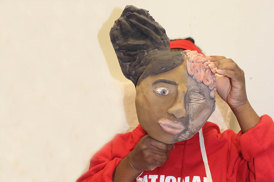 Female student holding a mask