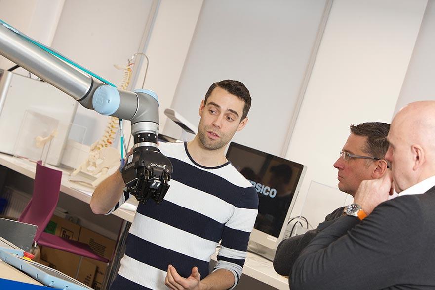Pepsico's Steven Brooks (left) presents Professor Philip Breedon with the robotic arm