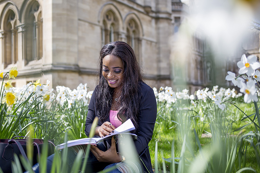 Student reading book on Arkwright lawn in the sun