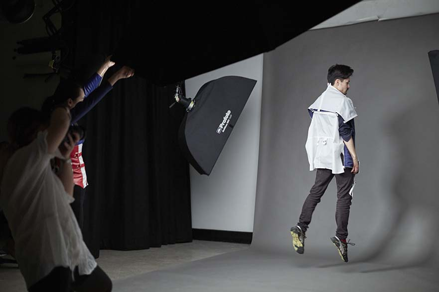 Male student jumping while being photographed in studio.