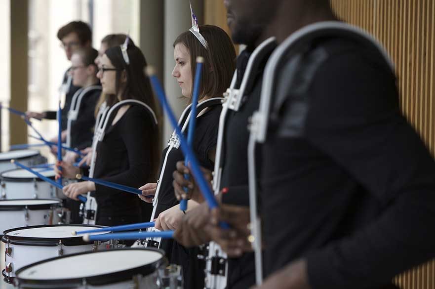Male and female students playing snare drums in a line.