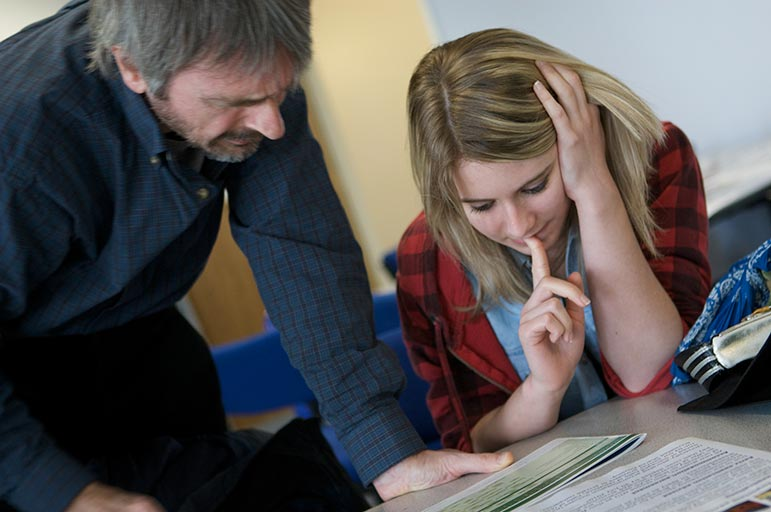 a student studying papers with her dad or carer
