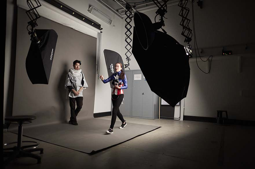 Male student posing for photo while female studio holds camera.