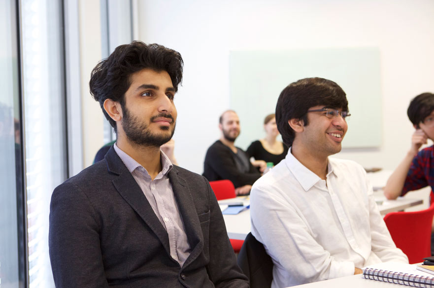 2 male entrepreneurs smiling in seminar