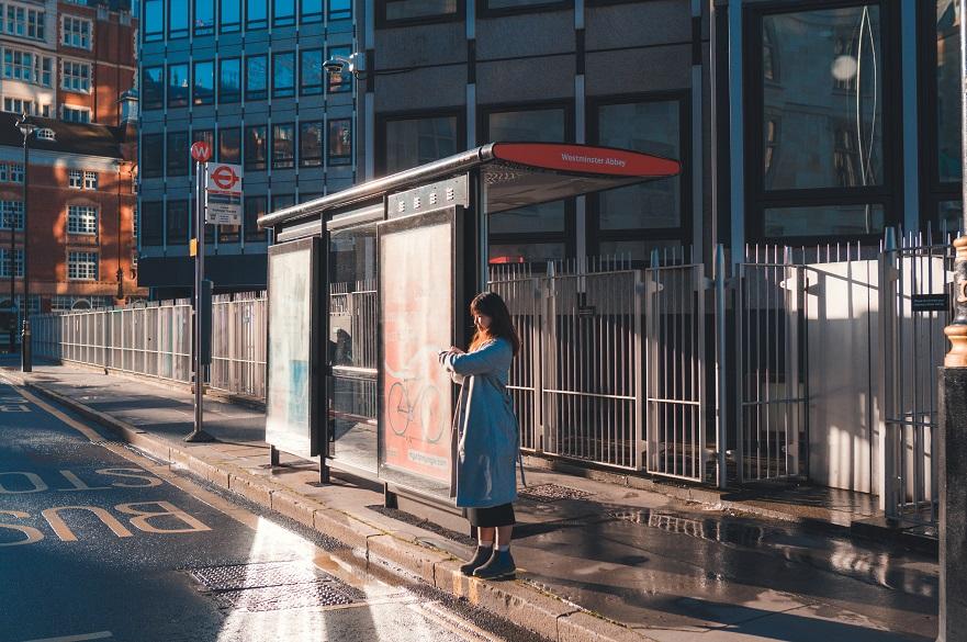 Woman waiting at a bus stop