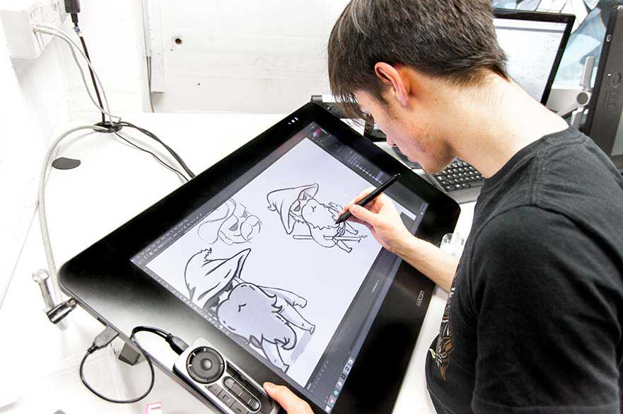 A male student working on a touch drawing screen.
