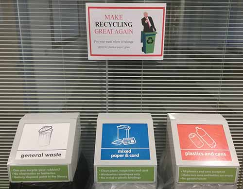 Waste segregation bins and a poster stating make recycling great again