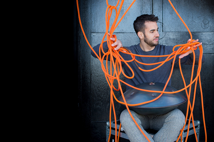 Manu Delago sat with his hang on his lap, and some orange rope in front of him.