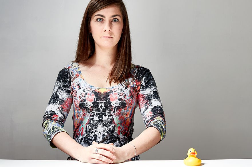 Bridie Squires looking at the camera with a plastic toy duck next to her.