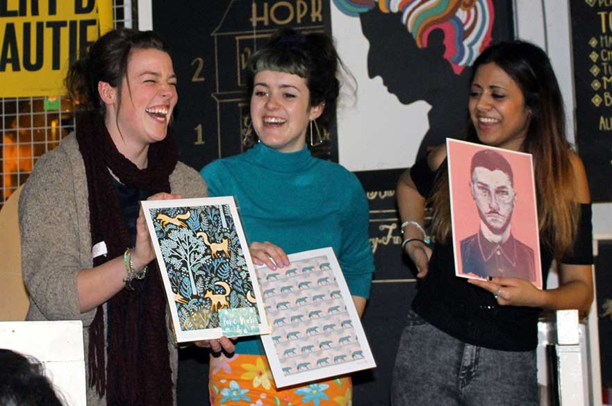Students show off their purchases at art auction