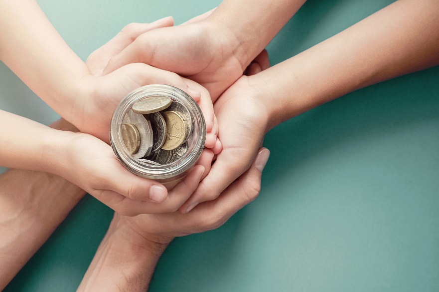 Hands holding a money jar