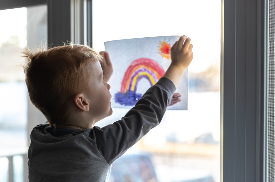Child putting a rainbow picture on the window