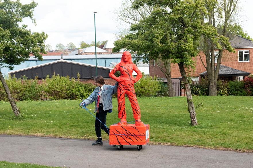 A woman is dragging a full-size human sculpture down a road