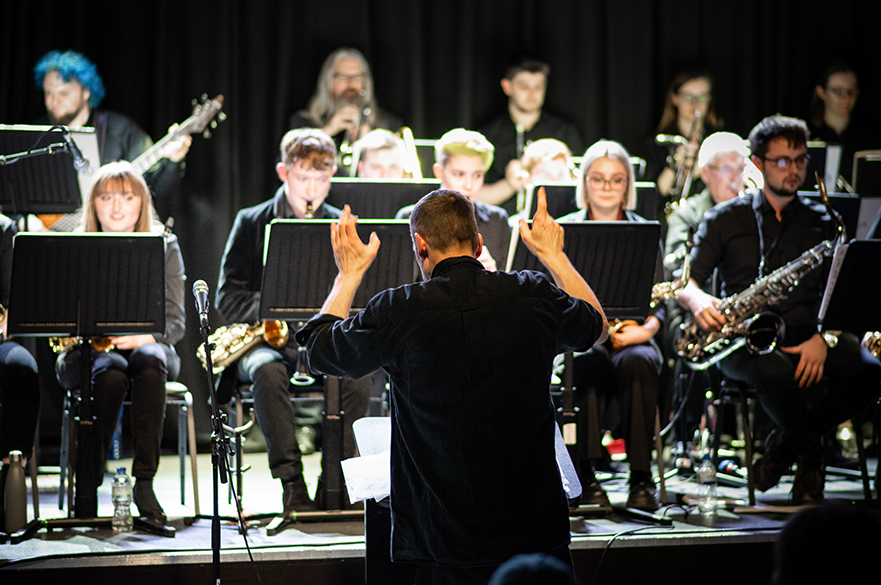 A Big Band on stage with a conductor.