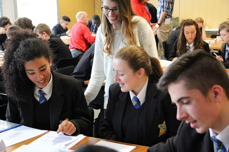 secondary school pupils talking at desk