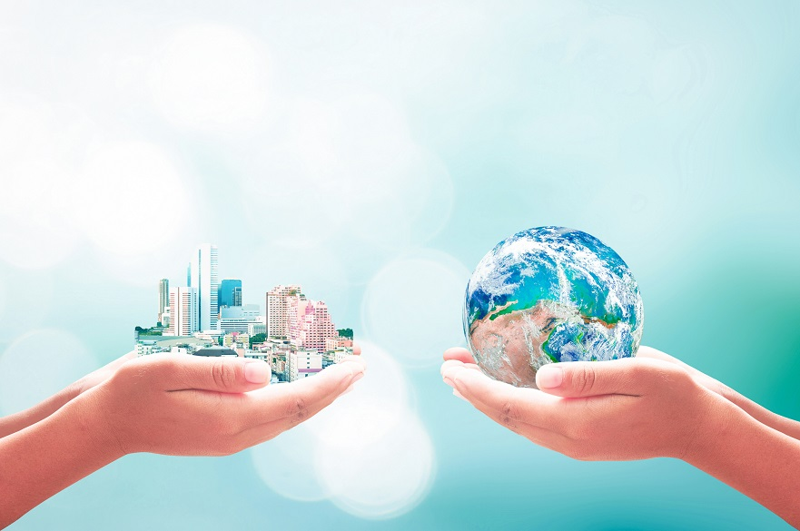 Hands holding a globe and a city