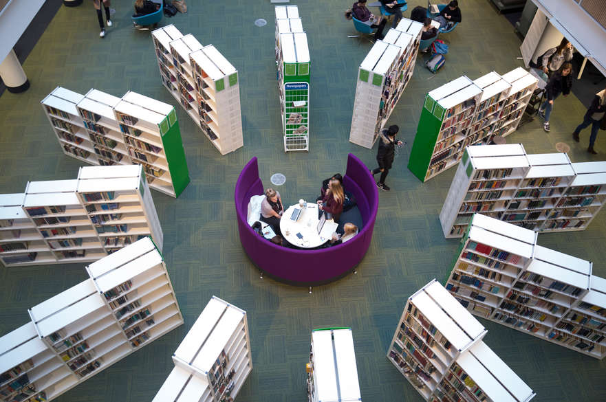 A birds eye view of Boots library, level 0. There is a round table with students sitting around it in the centre and book cases are laced in a circle around the table.