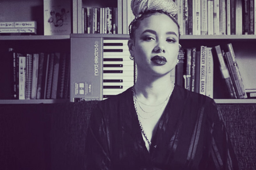 A photo of Natalie Duncan in front of a synth and a bookcase, in black and white.