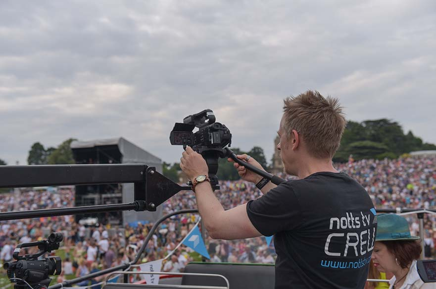 Film crew member at an outdoor event filming crowd