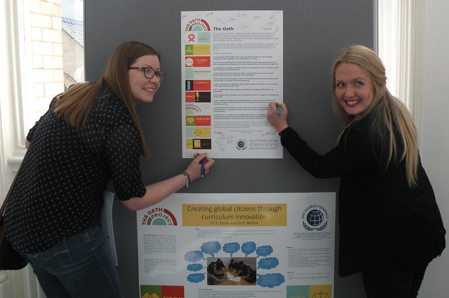 Students at the Sustainable Tourism event pose next to an exhibit