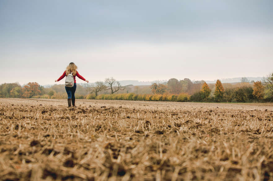 A blonde haired girl walking in a yellow-coloured field with her back to the camera. The girl's arms are stretched out at her sides and there are trees and fields in the horizon