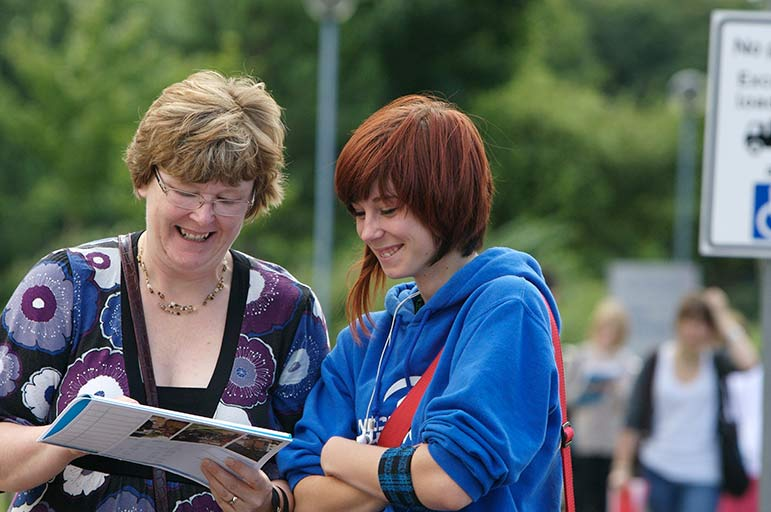 a student with a parent looking at a brochure