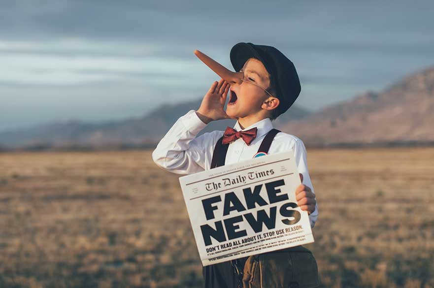 Boy with fake news newspaper