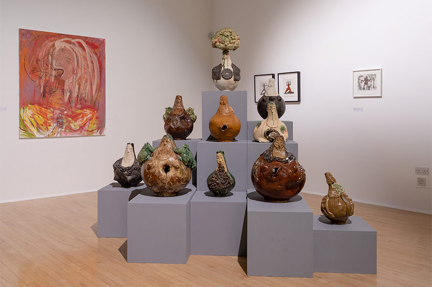 A collection of sculptures on plinth in a gallery with framed artwork on the walls. image