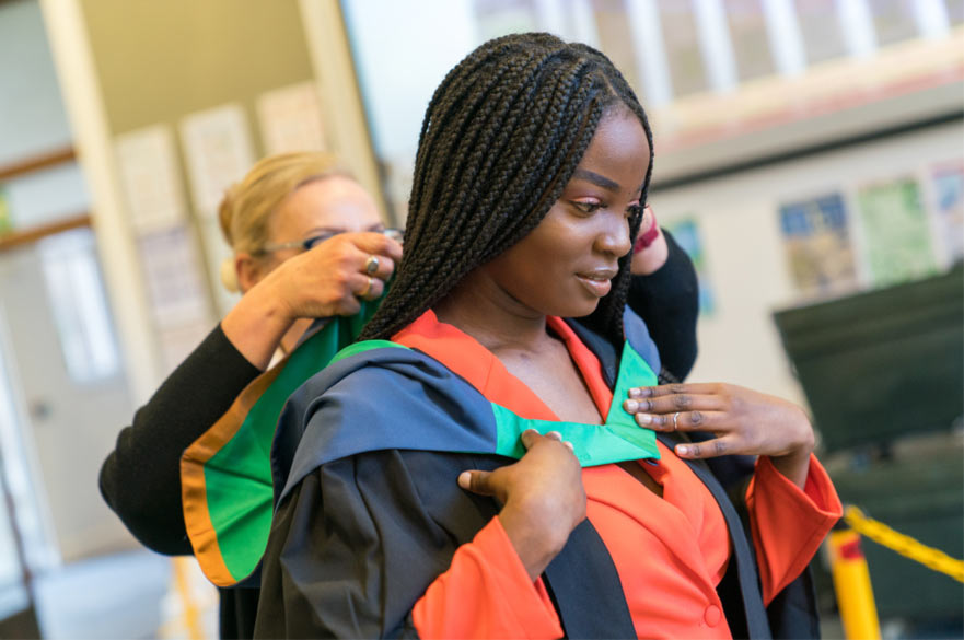 A student getting her graduation gown fitted over a striking orange suit.